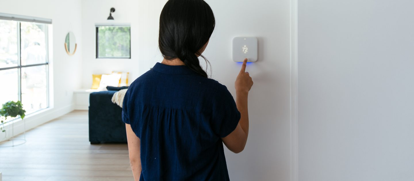 woman setting temperature with Vivint Element smart thermostat