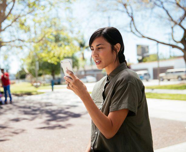 Woman checks water sensor on Vivint mobile app